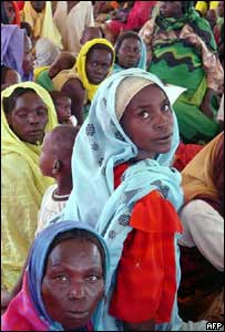 Women and children wait at a camp in Darfur