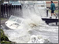 An unidentified man walks past a partially submerged boat at a yacht basin in Florida