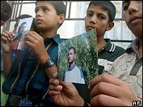 Palestinian boys in Damascus hold up Izz El-Deen Khalil's picture