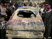 Residents gather around a car damaged in an US air strike in Sadr City, Baghdad, 27 September 2004