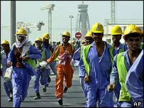 Construction workers run out of the Dubai Airport new terminal's construction site