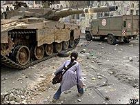 Palestinian schoolgirl passes an Israeli tank in Nablus