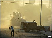 A Palestinian youth throws rocks at Israeli tanks in Nablus