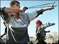 Palestinians fire stones at Israeli troops with slingshots in Ramallah in October 2000