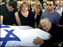 Woman weeps over coffins of two Israeli sisters killed in a suicide bombing in Tel Aviv in June 2001