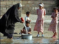 An Iraqi family collects water in Falluja