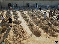 Iraqis gather around the graves of their relatives and friends killed during the fighting in football pitch turned into a cemetery