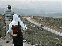 Lebanese civilians watch an Israeli jeep patrol the border