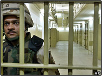 A US soldier guards cells inside Abu Ghraib prison