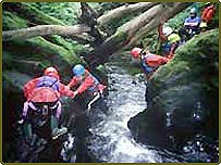 Children crossing a river in a team activity