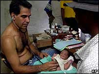 Venezuelan Air Force Doctor Jose Manuel Aguilar treats a three-day-old baby