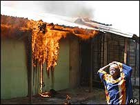 Girl running past burning building in Yelwa, May 2004