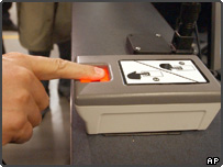Passenger using a machine that takes inkless fingerprints at JFK airport, USA.
