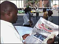 Zimbabwean man reading a newspaper