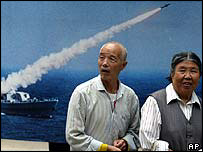 Elderly Chinese near billboard showing Chinese ship missile launch