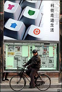Chinese man cycling past a billboard