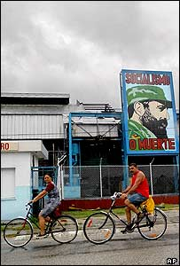 Cubans cycle past a poster of Fidel Castro, Havana