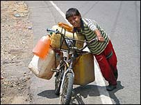 A 12-year-old boy transports petrol on his bicycle