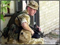 A British soldier takes up a position during a street patrol in the southern city of Basra, Iraq