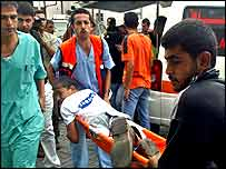 Palestinians carrying a wounded youth