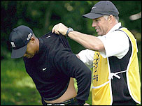 Tiger Woods has some cream rubbed into his injured back by caddy Steve Williams