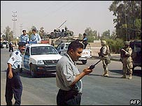 Iraqi police and US troops secure a street in Samarra on 9 September 2004