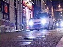 Cars being driven through Aberystwyth at night
