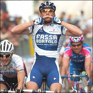 Fassa Bortolo's Alessandro Petacchi raises his arms as he wins stage one