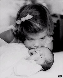Caroline Kennedy, daughter of President Kennedy, aged 3 kisses her baby brother in an image from 1961