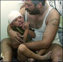 Man cradles injured son in Falluja, October 2 2004