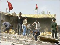 Iraqis clear rubble from destroyed office of wanted Shia cleric Moqtada Sadr in Baghdad