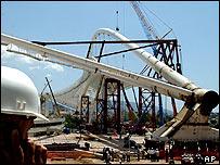 Santiago Calatrava's steel-and-glass arch rises slowly over the Olympic stadium