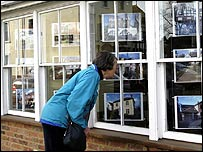 A woman looking in an estate agents window