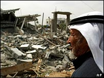 Palestinian man surveys the rubble of a home in Deir al-Balah, Gaza Strip