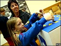 A girl puts her mother's ballot through the box in Ljubljana