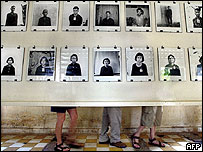Tourists standing behind a display of Khmer Rouge victim pictures in Phnom Penh (archive picture)
