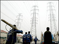 Workers walk below power lines near a power plant in Beijing