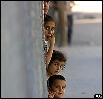 Palestinian children shelter in a doorway in Jabaliya camp
