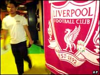Thai man walks past a Liverpool poster at a soccer shop in Bangkok, Thailand