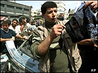 A Palestinian man holds a piece of blood-stained clothing from wreckage of car