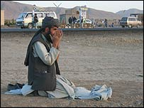 A man prays by the road on the Kabul to Kandahar highway through southern Afghanistan