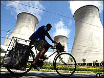 A cyclist rides past cooling towers at a power station on the outskirts of Beijing Wednesday, Aug. 4, 2004