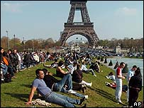 Tourists sit near the Eiffel Tower in Paris