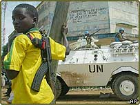 A child fighter of the rebel Union of Congolese Patriots stands near a United Nations armoured personnel carrier near the UN compound, in Bunia, Congo, 30 May 2003
