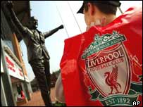 A Liverpool fan looks at the statue of former manager Bill Shankly outside the Anfield stadium