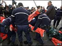 French police drag away Greenpeace protesters as they try to block a road to a nuclear reprocessing plant