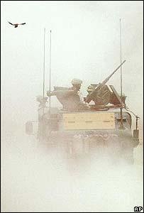 Un pájaro vuela sobre un tanque del ejército de EE.UU. en Irak que pasa por la cárcel de Abu Ghraib.