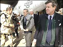 Donald Rumsfeld, centre, leaves a C-130 transport plane after being greeted by Paul Bremer, right, in Iraq on 23 February 2004