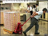 Bank of Japan worker pulls a stack of yen notes