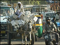 An Indian man transports his wares by horse in New Delhi's busy traffic
